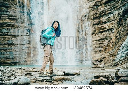 Traveler girl standing on background of waterfall and looking at camera outdoor