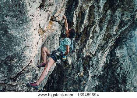 Young woman in safety harness with equipment started to climb the rock wall outdoor climber coating her hand in chalk magnesium