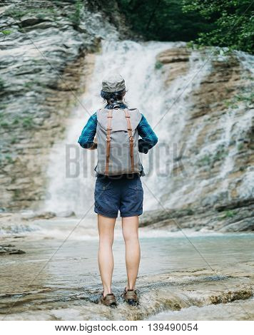 Traveler young woman with backpack standing in front of waterfall rear view