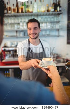 Customer taking coffee from happy young waiter at cafe