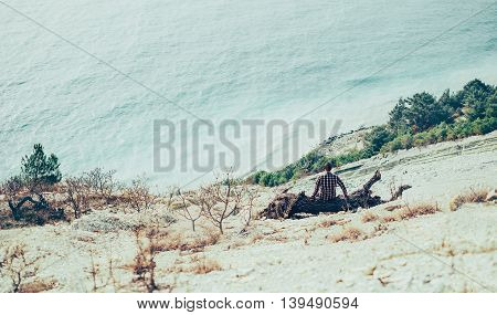 Young man sitting on snag on coast and enjoying view of sea. Toned image