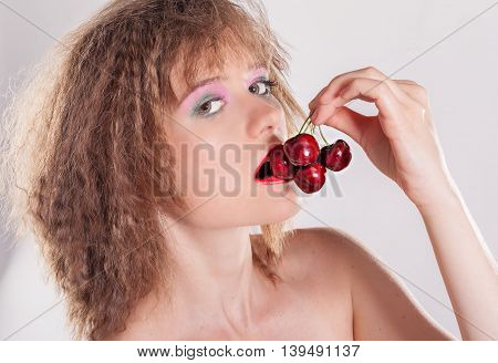 Cropped studio shot of a beautiful young woman with a cherry between her lips
