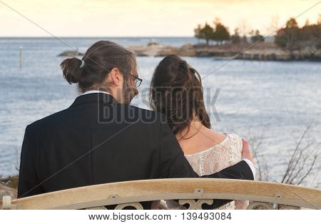 a bride and groom sitting on a bench outside overlooking Long Island Sound in Branford Connecticut.