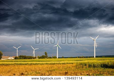 Dark clouds above field with Wind Turbines.