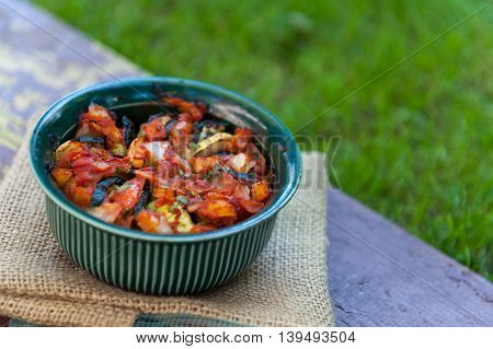 Small green casserole with ratatouille on a wooden table