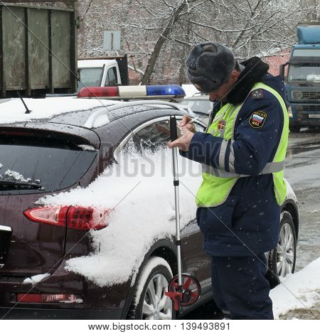 March 2013, Moscow, Russia. The inspector of police writes the Protocol of the infringer of rules of traffic