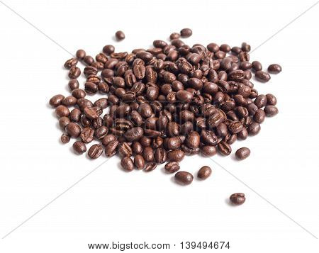 Selective focus on dark brown coffee beans pile isolated on white background