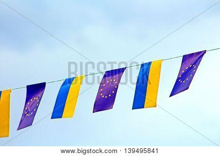 Flags of European Union and Ukraine over blue sky