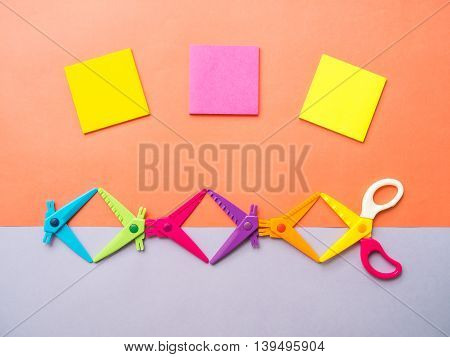 Top view of colorful set of zigzag changable art scissors and three sticky notes on two tone pastel orange purple background