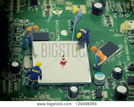 group of mini mechanic work on mainboard and CPU they try to open chip for repair - can use to display or montage on product