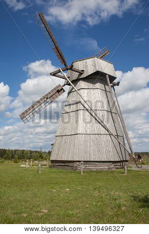 old wooden wind mill against cloudy sky