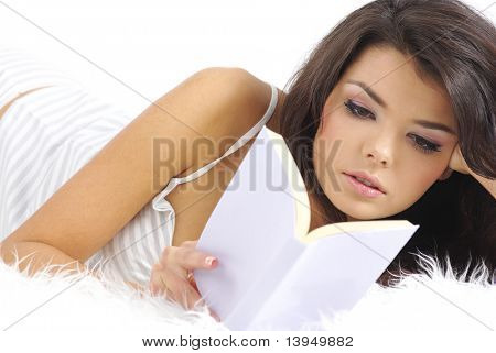 beautiful young woman reading book in bed