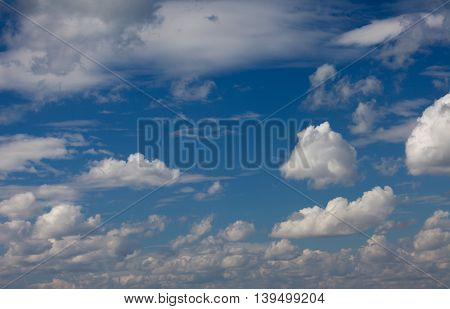 Deep blue sky and fluffy clouds background