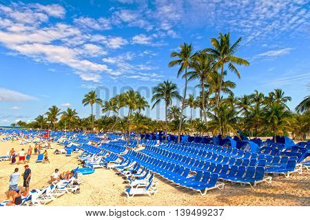 Great stirrup Cay Bahamas - -January 08 2016: public beach with many people on sandy coastline near green palm trees and chairs sunny day outdoor on natural blue sky background