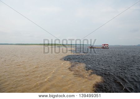 water meeting in brazil -amazon river with rio del negro. transfer boat with cars on deck floating on clean and dirty river water with different streams