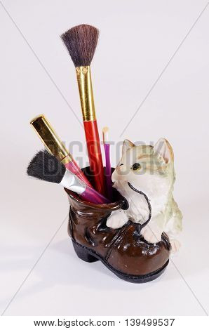 In a beautiful glass stand female cosmetic brush and pencil.