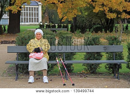 Old Woman With Crutches Is Sitting On A Bench