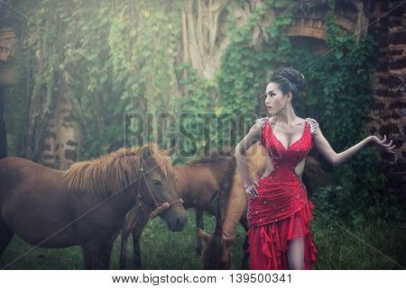 Portrait of a beautiful sexy fashion girl in a red dress on the nature of the park, with dark hair and a leather belt