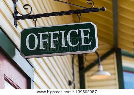 Hanging black office sign with white letters.