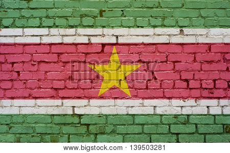 Flag of Suriname painted on brick wall background texture