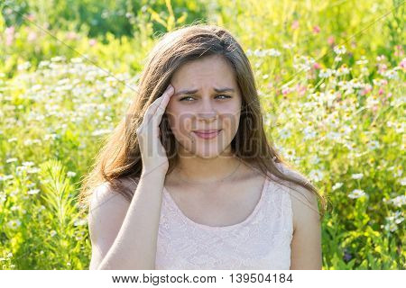 girl with a headache on a blossoming meadow