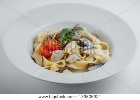 Tagliatelle With Chicken, Mushrooms And Tomatoes In A White Plate