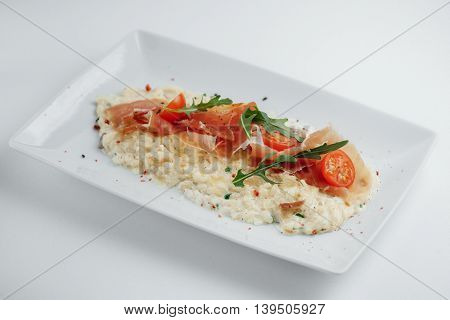 Risotto With Bacon, Tomatoes And Arugula On A White Plate