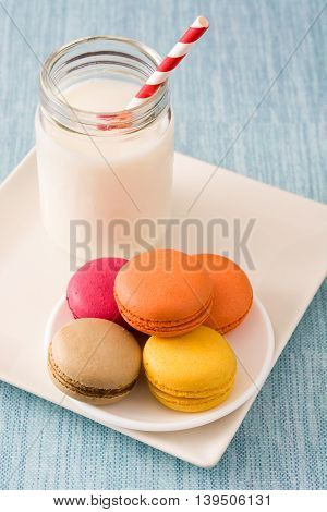 Milk and some sweet colored macaroons on blue background