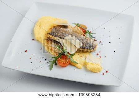 Fried Fish, Cheese, Tomatoes And Mashed Potatoes On A White Plate