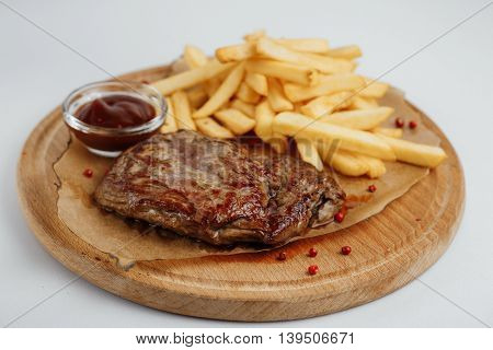 Steak With Fries And Sauce On A Wooden Tray