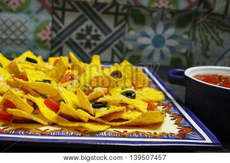 A plate of delicious tortilla nachos with melted cheese sauce chives onion black olives salsa on traditional mexican ornamental background