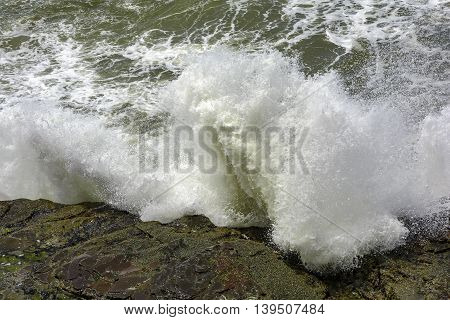 Waves breaking on the stone during a day of rough seas