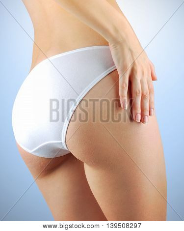 Beautiful slim female buttocks isolated on blue background