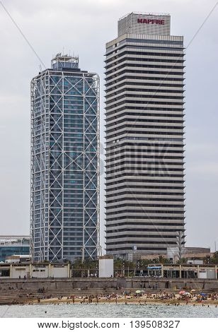 BARCELONA SPAIN - JULY 7 2016: Skyscrapers Torre Mapfre in the Olympic Port. It is named after its owner Mapfre an insurance company.