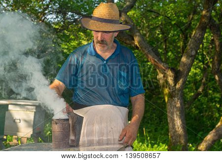 Portrait of Ukrainian bee-keeper with fuming smoker at work place