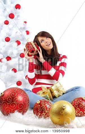mujer joven con caja de regalo junto al árbol de Navidad blanco