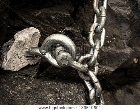 Steel Bolt Anchor Eye In Hard Basalt Rock. End Of Steel Chain