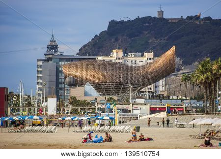 BARCELONA SPAIN - JULY 13 2016: Frank Gehry's modern El Peix d'Or sculpture is located in Barcelona's Vila Olimpica.
