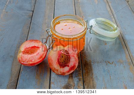 Jar with peach jam on the rustic wooden table.