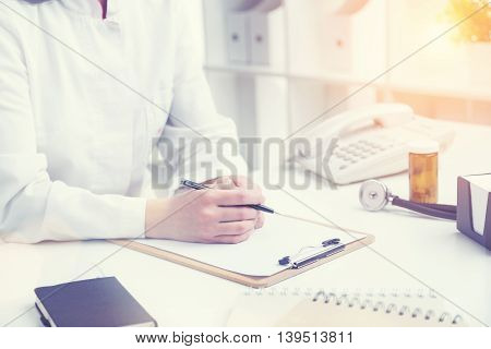 Doctor sitting at table ready to make notes only hands seen. Office. Concept of work. Toning image