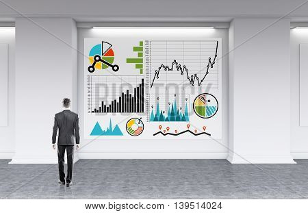 Businessman in gray suit standing in front of big whiteboard with sketches of graphs on it developing new strategy for his firm. Concept of finding sloution. 3d rendering.