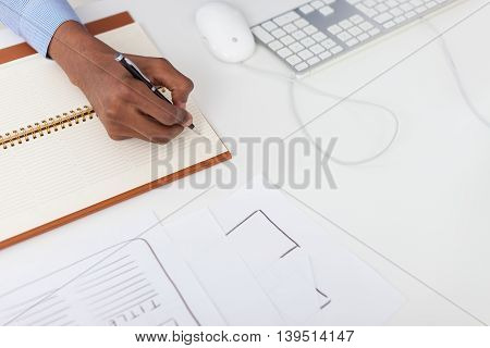 Black man hand writing in notebook. Computer mouse and keyboard near him on table. Concept of office work and decision making. Top view