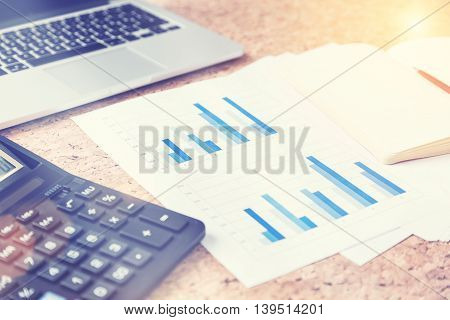 Closeup of cork table with keyboard calculator business report and blank copybook with pen. Toned image