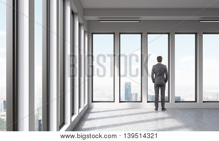 An adult watching at city out of large window in empty room. Concept of deep thinking. 3D render.