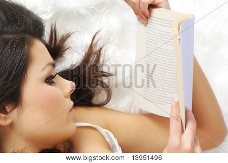 Closeup portrait of a happy young woman with a book in her hand