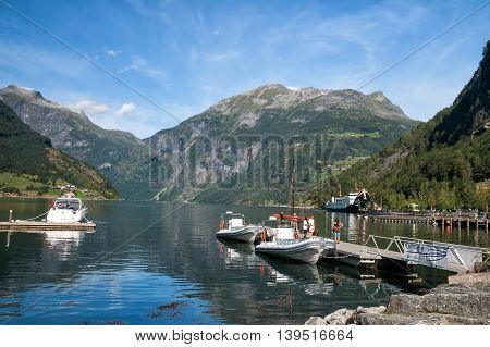 GEIRANGER NORWAY - AUGUST 13 2011: Tourists stand on a pier near the pleasure boats. Tours of the Geirangerfjord
