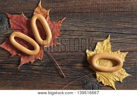 Tasty oval bagels on old wooden background with autumn leaves top view