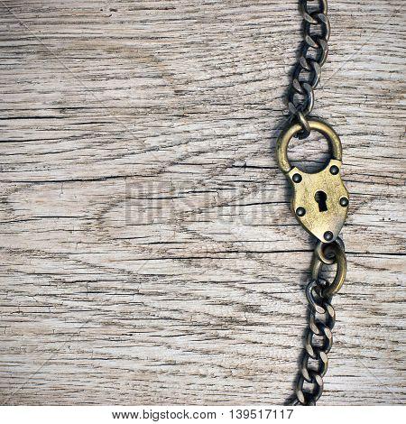 Old bronze lock on grunge wood background