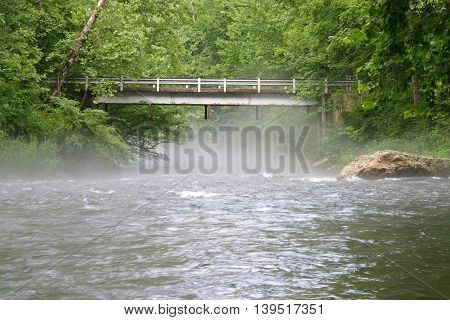 fog rises from the Nantahala River in North Carolina near a bridge.