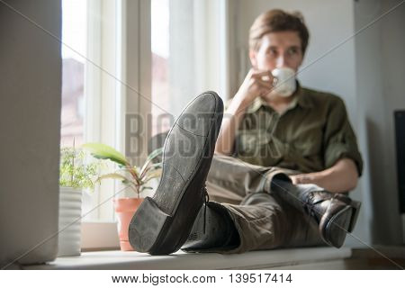 romantic pensive man with cup of coffee sit on the window